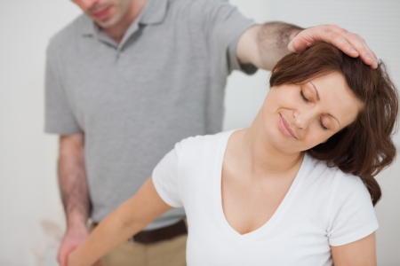 Smiling woman being stretched by a physiotherapist in a room