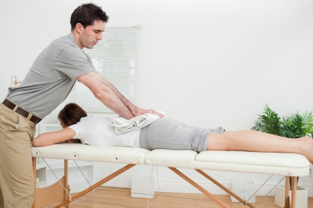 Woman lying while being massaged with a towel in a room