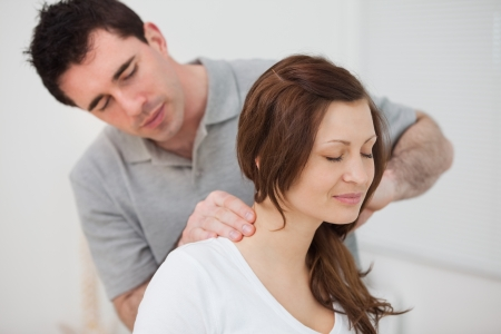 Smiling woman sitting while being massaged by a man in a room