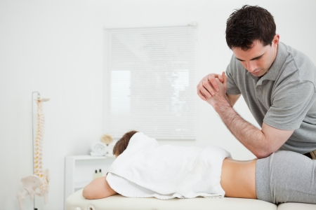 Brunette physiotherapist massaging a woman with his elbow in a room