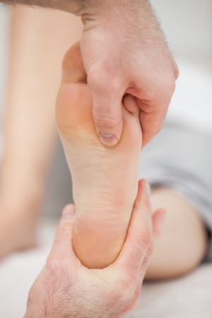 Doctor pressing his thumb on a foot in a room