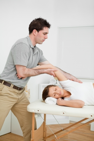 Serious doctor making a manual stretching in a medical room