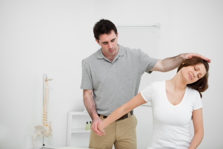 Osteopath stretching the arm of a woman in a medical room