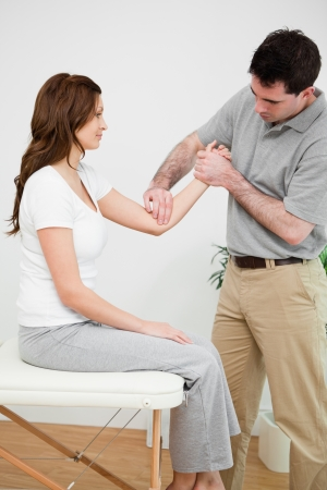 Serious physiotherapist touching the elbow of a woman in a room