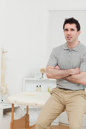 Peaceful osteopath sitting with arms crossed in his medical room