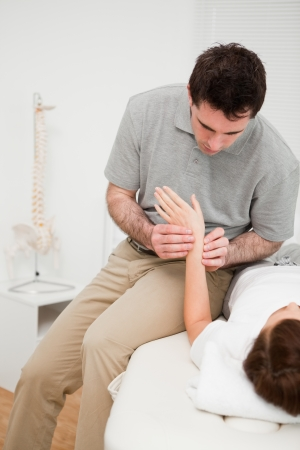 Physiotherapist placing his fingers on the hand of a patient in a room