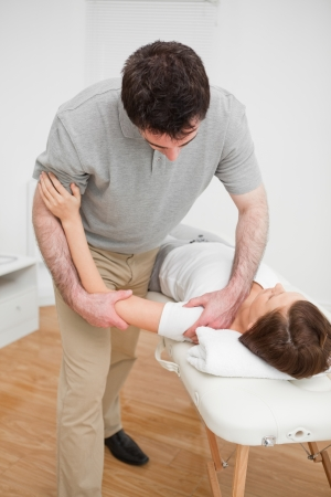 Osteopath working on a shoulder of a patient in a room