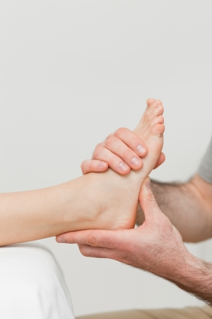 Hands of a physiotherapist massaging a foot in a room