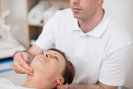 Physiotherapist pressing two fingers on the neck of his patient in a room