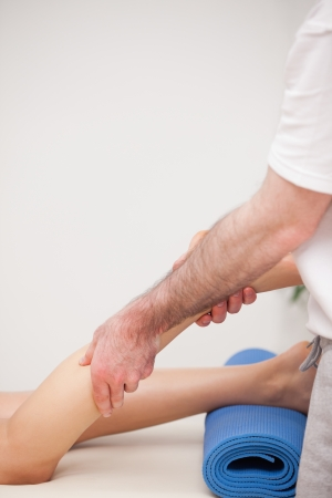 Podiatrist massaging the leg of his patient while standing in a room