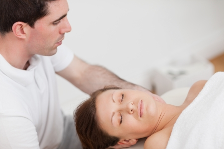 Masseur massaging the neck of his patient  in a room