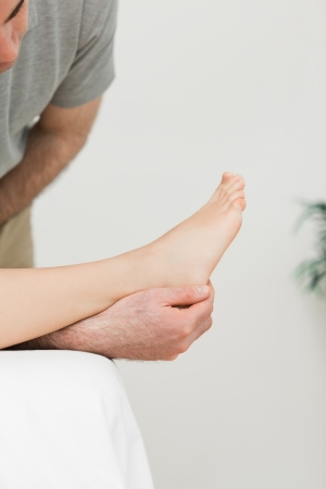 Podiatrist examining the foot of his patient in a room