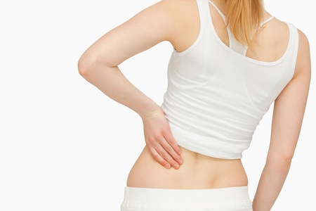 Woman standing while massaging her back against white background