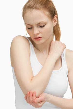 Woman touching her elbow against white background