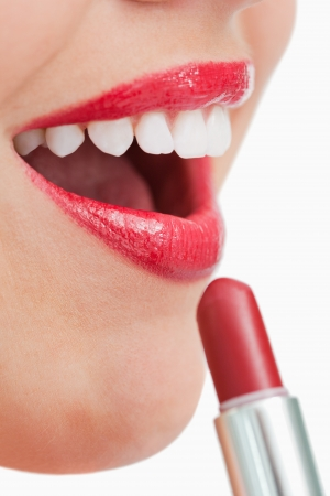 Woman opening her mouth while applying lipstick on her lips against a white background