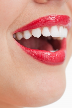 Close-up of the lips of a happy woman against a white background