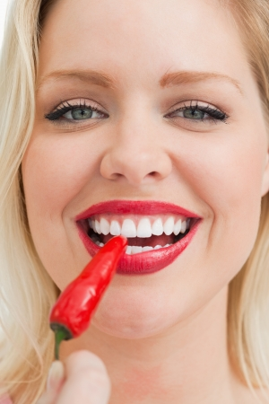Happy blonde woman eating a chili against a white background