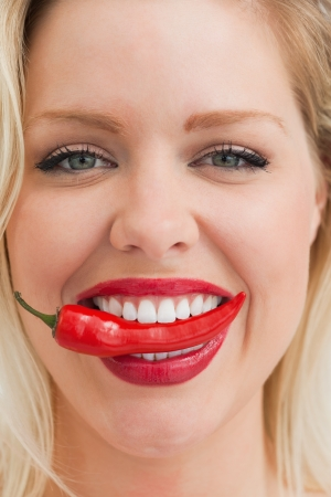 Close-up of a cheerful blonde woman placing a chili between her teeth