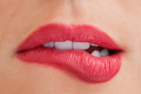 Close-up of an attractive woman biting her beautiful lips