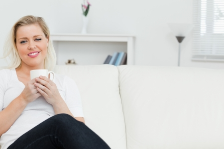 Woman on a sofa drinking a coffee in a lounge