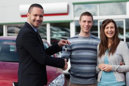 Photo pour Salesman shaking hand of man in a dealership - image libre de droit