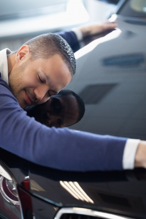 Man embracing a car in a garage