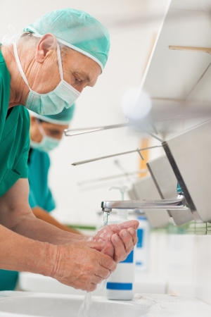 Photo pour Surgeons washing their hands in a sink - image libre de droit