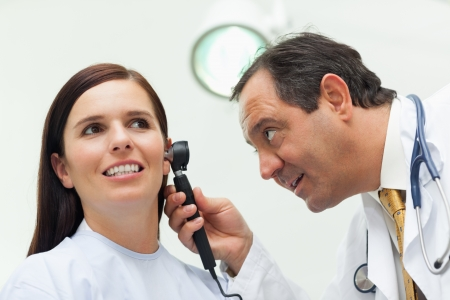 Doctor using an otoscope to look at the ear of his patient in an examination room