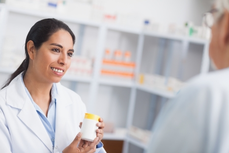 Pharmacist holding a drug box while looking at a patient in hospital