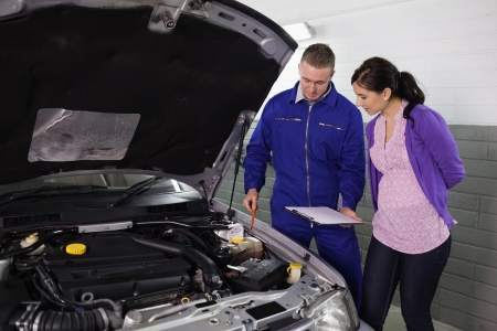 Mechanic showing a par of the engine to a woman in a garage