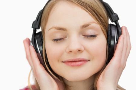 Photo pour Close up of a woman with headphones against a white background - image libre de droit