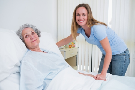 Woman holding the hand of a patient in a hospital room