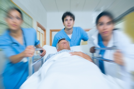 Team of doctor running in a hospital hallway with a patient in a bed