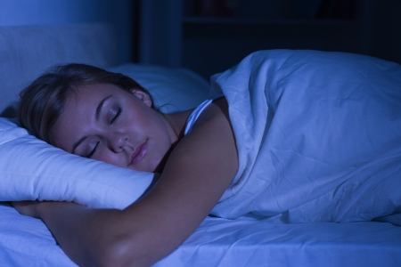 Photo pour Serene woman sleeping at night in the bedroom - image libre de droit
