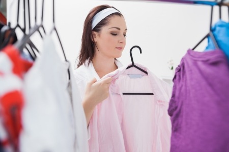 Young woman holding shirt in front of wardrobe