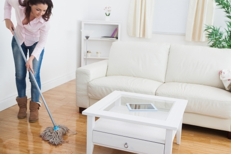 Young woman  mopping living room floor