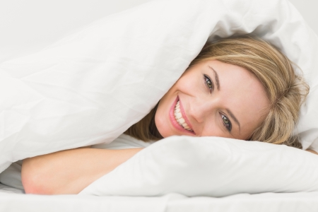 Photo for Portrait of happy beautiful young woman in bed at home - Royalty Free Image