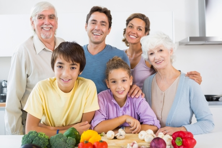 All the family smiling in kitchen in front of chopping board with vegetables