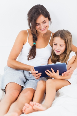 Mother and her daughter using a tablet on the bed