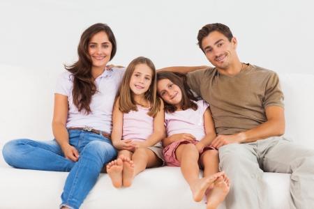 Foto de Cute family sitting on a sofa in the living room - Imagen libre de derechos