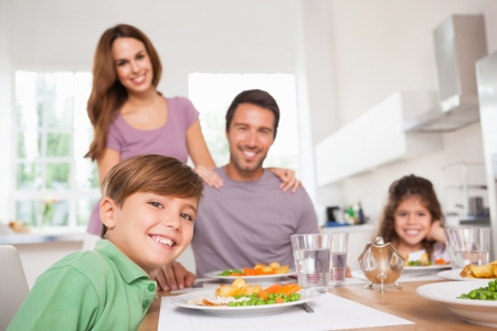 Foto de Family looking at the camera at dinner time in kitchen - Imagen libre de derechos