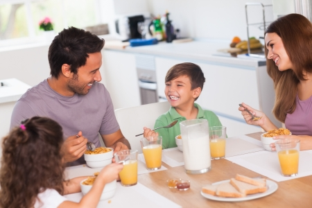 Foto de Family laughing around breakfast in kitchen - Imagen libre de derechos