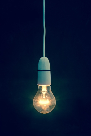 Light bulb turned on over black background
