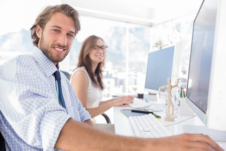 Attractive designers at work at their desk in modern office