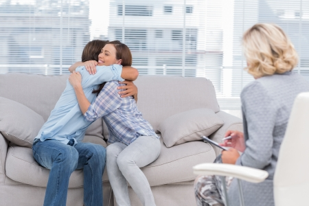 Young couple cuddling on the couch while therapist watches