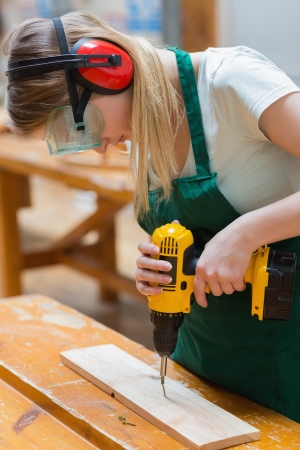 Student using the drill while standing in a woodworking class and drilling a hole