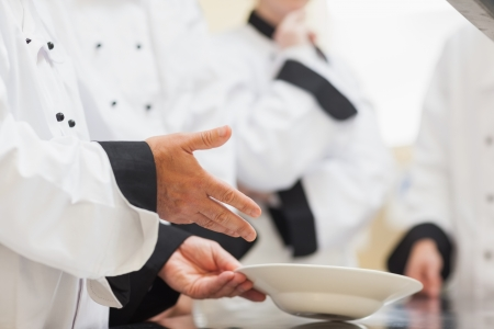 Head chef showing class a bowl in the kitchen on a counter
