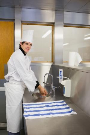 Photo pour Smiling chef washing hands in the restaurant - image libre de droit