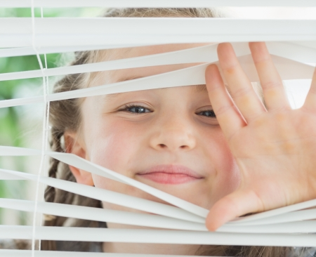 Smiling girl looking through the white window blinds