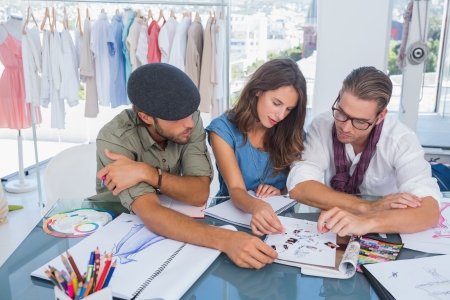 Three fashion designers working on desk in a bright office